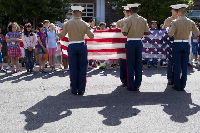 """Barcroft Elementary School fourth grade students watch as Marines from Headquarters and Service Battalion, Headquarters Marine Corps, Henderson Hall take part in the Partners-in-Education Flag Day ceremony June 14 in Arlington, Va. The flag, which had previously flown over the Marine Corps War Memorial, was later presented to Barcroftsh""""ôs retiring principal, Miriam Hughey-Guy."""