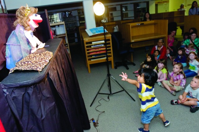 Mario Burgos, 3, wants to say hello to a queen puppet performing in the story The Princess and the Pea at the Kaydee Puppets show at the Van Noy Library on Friday, June14.
