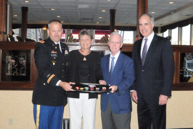U.S. Senator Robert P. Casey, Jr. (right) and Col. Eric Lawson (Left) from the 316th Sustainment Command (Expeditionary) present, Vietnam veteran, John Ferry (center) of Seven Fields, Pa., with his Bronze Star, Combat Infantryman Badge and seven other awards at a ceremony in Pittsburgh on June 21. After a 42 year wait, Ferry received his awards by requesting assistance from Senator Casey's office. Ferry was accompanied by his wife Carol (center) for the ceremony.