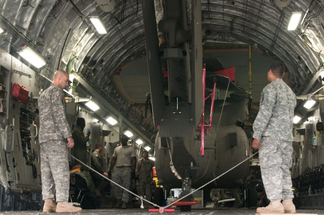 Chief Warrant Officer 2 Jarone Amarino (left), a Blackhawk pilot, and Sgt. Robert Saludares (right), a Blackhawk mechanic with Detachment 1, Charlie Co., 207th Aviation of the Hawaii Army National Guard, prepare to unload the UH-60 Blackhawk from the C-17 Globemaster III after landing in Halim Perdanakusuma Airport, Indonesia, June 16, 2013. The Guardsmen will take part in Exercise Garuda Shield 13 with air support via VIP escort and Medevac assistance from the UH-60, and paratrooper drops from the C-17's crew stationed at Joint Base Pearl Harbor-Hickam.