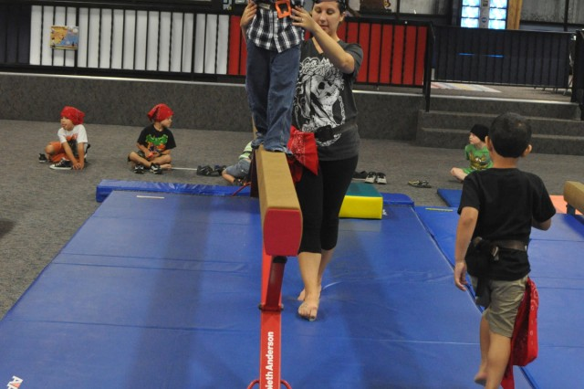 "With help from Capt. Lacey Clark, pirate David ""Redbeard"" Wiser, 6, walks the plank Tuesday morning at the SkiesUnlimited Pirate Camp."
