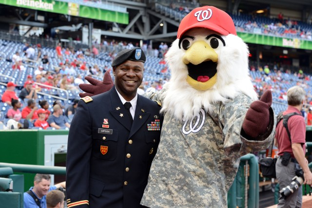 Lt. Col. Isaac Gipson enjoys a moment with the Washington Nationals mascot Screech before the re-enlistment ceremony for Soldiers at Army Day at Nationals Park, in Washington, D.C., June 20, 2013.