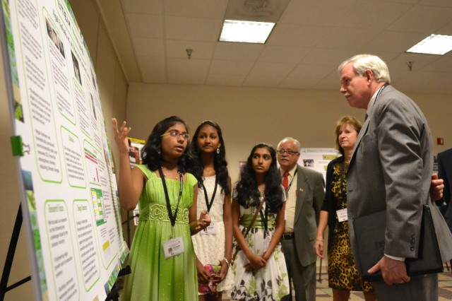 "Seventh-grader Divya Mereddy explains the project of her team, ""STEM Ninjas,"" to Lloyd Caldwell, director of military programs for the U.S. Army Corps of Engineers, with teammates Rachana Subbanna and Sneha Thandra. The Corps' director of human resources, Sue Engelhardt, and Fidel Rodriguez look on. The STEM Ninjas won first place on June 21, 2013, for their grade in the 11th Annual eCYBERMISSION National Judging and Education Event. (Photo by Evan Dyson, U.S. Army Corps of Engineers Public Affairs)"