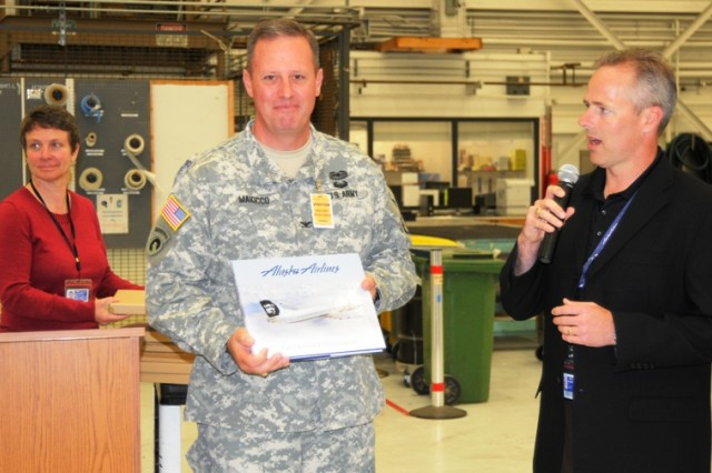 Col. Fred Maiocco accepts a book about Alaska Airlines' history on behalf of the 364th Expeditionary Sustainment Command.