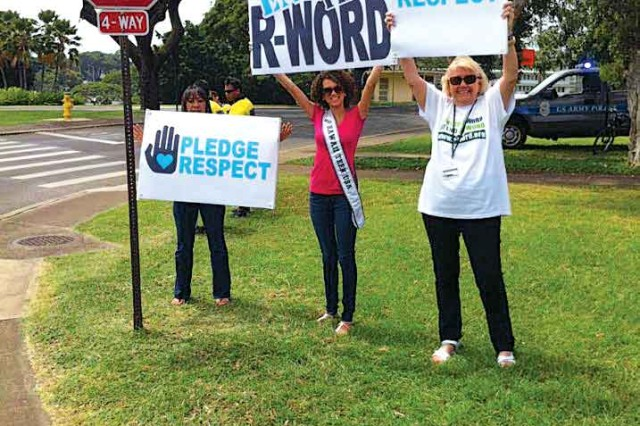 Samantha Neyland (center) helps wave signs with Family and Morale, Welfare and Recreation and Special Olympics during the R-Word Rally, conducted by the garrison's Exceptional Family Member Program, March 25.