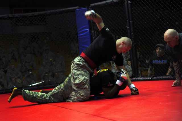 U.S. Army Sgt. Colter Brown, top, with Headquarters and Headquarters Battalion, applies finishing punches to Spc. Daniel Anderson with 1st Squadron, 73rd Airborne Cavalry Regiment, 2nd Brigade Combat Team, during the 82nd Airborne Division's All American Week combatives tournament at Fort Bragg, N.C., May 22, 2013.  (U.S. Army photo by Sgt. Joseph Guenther/Released)