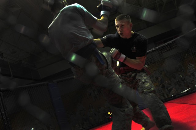 U.S. Army Sgt. Jesse Hertzog, right, representing Headquarters and Headquarters Battalion, strikes Pfc. Charles Curtis with 1st Battalion, 504th Parachute Infantry Regiment, 1st Brigade Combat Team, as they compete for the first-place title for the 140-pound weight class at the 82nd Airborne Division's All American Week combatives tournament at Fort Bragg, N.C., May 22, 2013. Hertzog won first place, and was also the 2011 155-pound All Army combatives tournament champion.  (U.S. Army photo by Sgt. Joseph Guenther/Released)