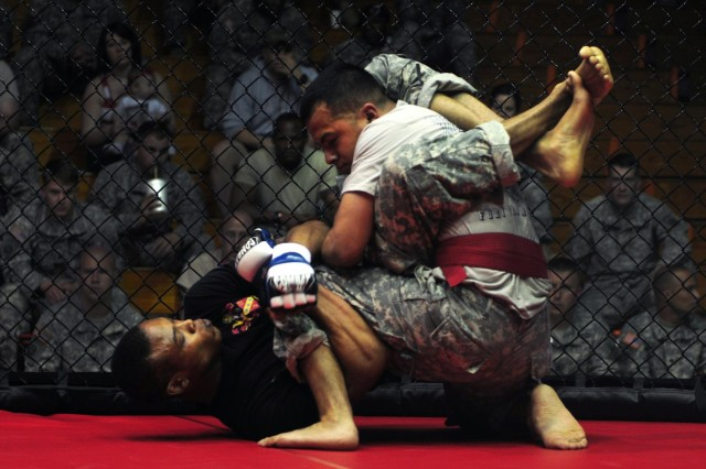 U.S. Army Spc. Johnny Johnson, left, with 2nd Battalion, 319th Airborne Field Artillery Regiment, 2nd Brigade Combat Team, and Sgt. Crisoforo Trujillo, right, with 4th Brigade Special Troops Battalion, struggle to gain a dominant position as they compete for the third-place title for the 155-pound weight class at the 82nd Airborne Division's All American Week combatives tournament at Fort Bragg, N.C., May 22, 2013.  (U.S. Army photo by Sgt. Joseph Guenther/Released)