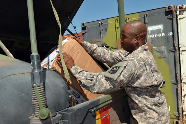 U.S. Army Spc. Anthony Atunku, a member of 1st Squadron, 38th Cavalry Regiment, packs up a box of supplies meant for Gate One at Camp Novo Selo June 17. The supplies helped to improve the Morale, Welfare, and Recreation opportunities for the soldiers at the post. (Photo by Staff Sgt. Cody Harding, 4th Public Affairs Detachment)