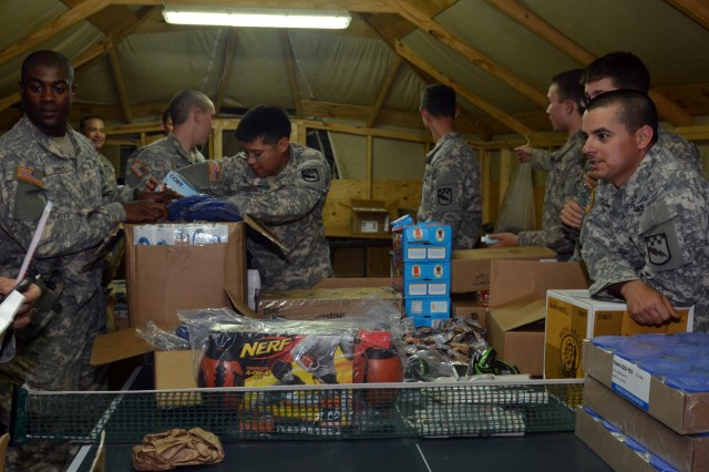Soldiers with Company C, 1st Squadron, 38th Cavalry Regiment, open boxes of Morale, Welfare and Recreation supplies brought up from Camp Novo Selo to the Gate One MWR tent June 17. The supplies helped improve the variety of activities soldiers can take part in during their free time. (Photo by Staff Sgt. Cody Harding, 4th Public Affairs Detachment)