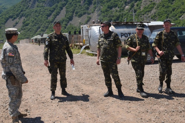 U.S. Army Staff Sgt. Jesse Harris, the 'mayor' of Gate One and a soldier with Company C, 1st Squadron, 38th Cavalry Regiment speaks with members of the Ukrainian Engineering Coy on the upcoming road improvement project for Gate One June 18. The Ukrainian Coy began dropping off over 1,000 cubic meters of gravel for the post to help improve the roads on the small camp. (Photo by Staff Sgt. Cody Harding, 4th Public Affairs Detachment)