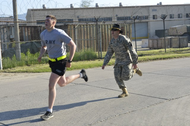 A spur holder motivates a candidate during a four-mile run, May 21, 2013. As one of the featured tasks of the spur ride, spur candidates were required to complete the four-mile run in less than 36 minutes. (U.S. Army photo by Sgt. Wayne Diaz, 1st ABCT, PAO)