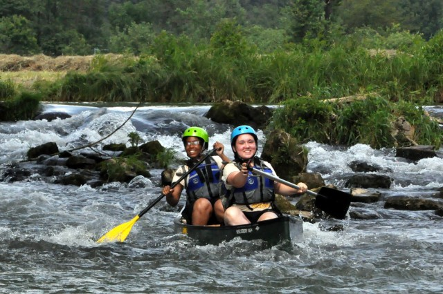 Vilseck High School JROTC cadets Shanice Arnold (left), and Jocelyn Nichols ride the waves of the Wiesent River during the Cadet Leadership Challenge in Grafenwoehr, Germany, June 18.