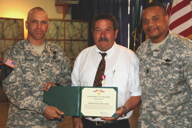 """The U.S. Army Garrison Ansbach commander, Col. Kelly J. Lawler, and USAG Ansbach command sergeant major, Command Sgt. Maj. Leeford C. Cain, present Rudolf """"Rudi"""" Leykauf the Superior Civilian Service Award for his 46 years of service to the United States."""