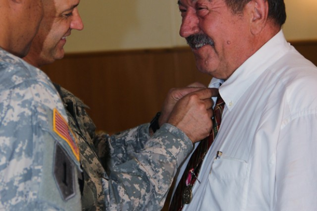 """Rudolf """"Rudi"""" Leykauf receives his retirement pin for his 46 years of service from the U.S. Army Garrison Ansbach commander, Col. Kelly J. Lawler."""