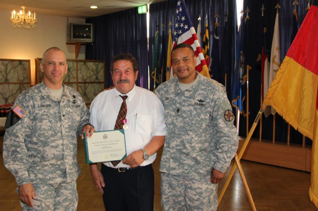 """Rudolf """"Rudi"""" Leykauf receives his certificate of retirement June 21 from the U.S. Army Garrison Ansbach commander, Col. Kelly J. Lawler, and USAG Ansbach command sergeant major, Command Sgt. Maj. Leeford C. Cain."""