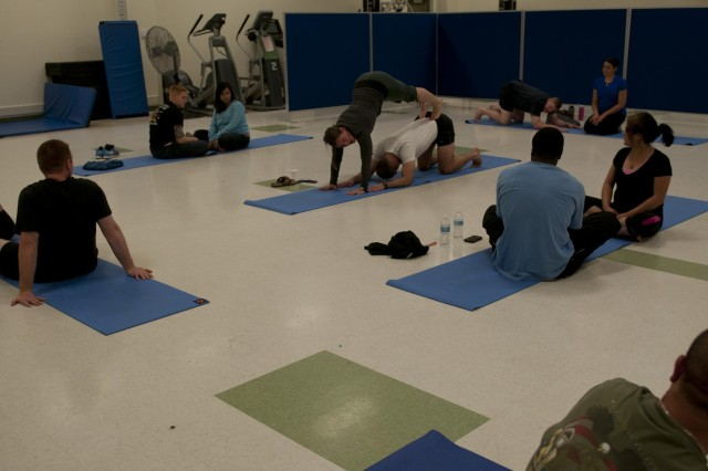 Sarah Brown, certified athletic trainer and yoga instructor with Soldier 360, and Col. John Meyer, currently a student at the Naval War College preparing for command of an infantry brigade, instruct Soldier 360 students and their spouses on the proper way to execute a couple's yoga pose. The Soldier 360 program is a five day course of instruction ranging from stress management and communication to domestic violence and sexual assault. (Photo by Staff Sgt. Bryan Dominique, 2nd Bde., 2nd Inf. Div.)
