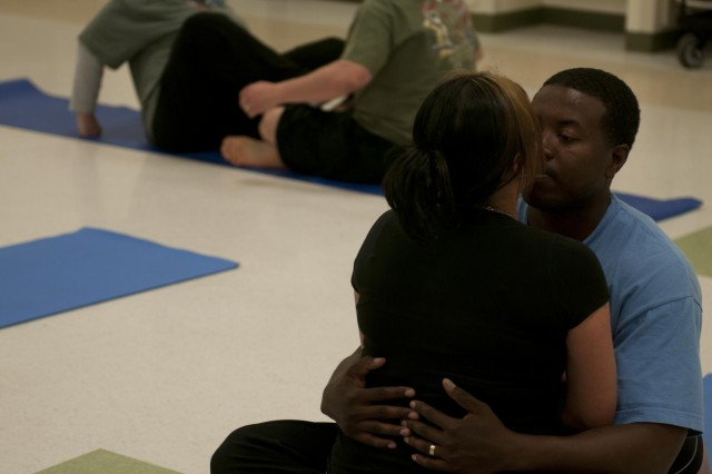 Sgt. Alvin Mathis, a noncommissioned officer with Company A, 2nd Brigade Support Battalion, 2nd Infantry Division, kisses his wife Jessica Mathis during couples yoga. Couple's yoga is part of the curriculum for the Soldier 360 course Sgt. Mathis was participating in. (Photo by Staff Sgt. Bryan Dominique, 2nd Bde., 2nd Inf. Div.)