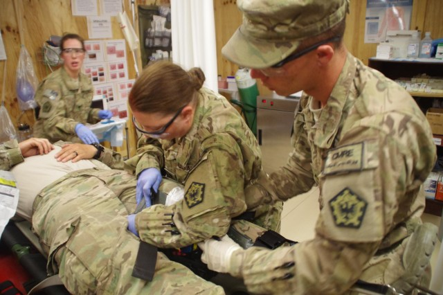 During a forward operating base-wide MASCAL exercise, Spc. Tammy Hyden, a medic in the 864th Engineer Battalion, CMRE, helps a patient in her battalion's trauma room.
