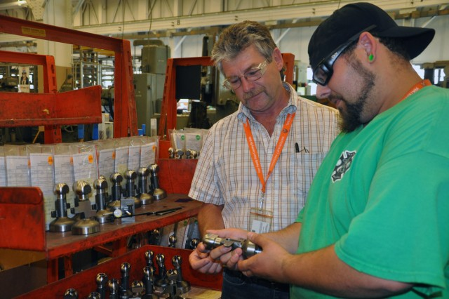 Arsenal General Foreman Paul Nieckarz, left, discussing 60 mm mortar basecap production with Jim White, a 4th-year apprentice who will complete his program this August.