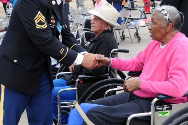 SAN ANTONIO - Sgt. 1st Class Angel Ortiznieves, platoon sergeant, Headquarters Support Company, Headquarters and Headquarters Battalion, Army North (Fifth Army), greets a resident of the Retama Manor Nursing Center, June 14, during a Flag Day Ceremony in Alamo City. Ortiznieves, event organizer and monthly volunteer, coordinated the event to honor the more than 30 Armed Forces veterans who reside at the manor.