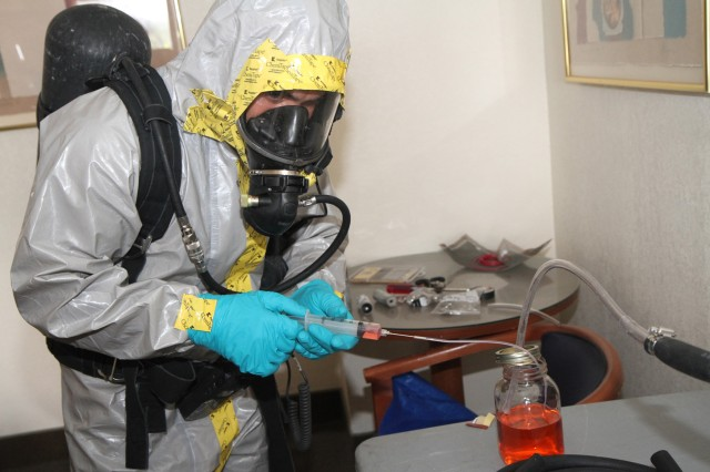 Sgt. Noah Devoux, a chemical, biological, radiological and nuclear specialist with the 44th Chemical Company, 2nd Chemical Battalion, 48th Chemical Brigade, takes a sample of an unidentified liquid that was found in a lab of an abandoned hotel, June 12, 2013, during his unit's Defense CBRN Response Force training exercise, in Killeen, Texas. Devoux was part of a reconnaissance team that found a homemade mustard gas lab in one of the hotel's rooms. The team took a sample of the liquid so it could be analyzed to determine if it was hazardous. The 44th Chem. Co. has been designated as part of the Department of Defense's Defense Chemical, Biological, Radiological and Nuclear Response Force for this fiscal year, as well as next fiscal year. U.S. Army North (Fifth Army)'s Civil Support Training Activity-Central was on hand to provide training for the company before conducting their annual certification, which took place June 14.