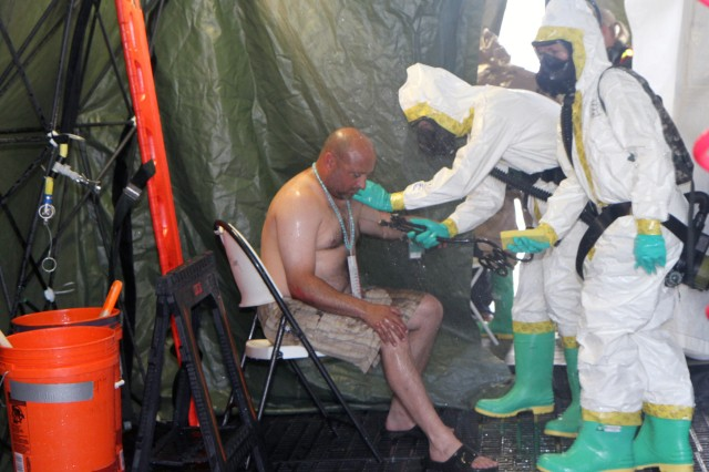 Spc. Timothy Gallup (center), 44th Chemical Company, 2nd Chemical Battalion, 48th Chemical Brigade, rinses off Michael Ratterman, one of the role players, during a mass casualty decontamination exercise, June 12, 2013, at the Skylark Airfield in Killeen Texas, while Pvt. Stephanie Emerick (right), 566th Area Support Medical Company, 61st Multifunctional Medical Battalion, 1st Medical Brigade, stands by with a sponge to wash him. The units were conducting decontamination training under the watchful eyes of the Civil Support Training Activity-Central from U.S. Army North (Fifth Army), in preparation for the 44th Chem. Co. training proficiency evaluation, which will allow the unit to remain on the Defense Chemical, Biological, Radiological and Nuclear Response Force mission for another year.