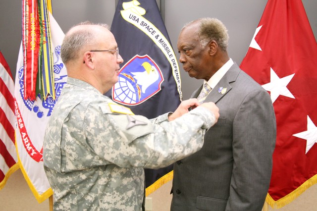 Lt. Gen. Richard P. Formica, commanding general, U.S. Army Space and Missile Defense Command/Army Forces Strategic Command, pins the Meritorious Civilian Service Award onto Thaddus Small, Information Assurance program manager, SMDC G-6, during Small's retirement June 20 at the command's Redstone Arsenal, Ala., headquarters. Small retires with 27 years of civilian service.