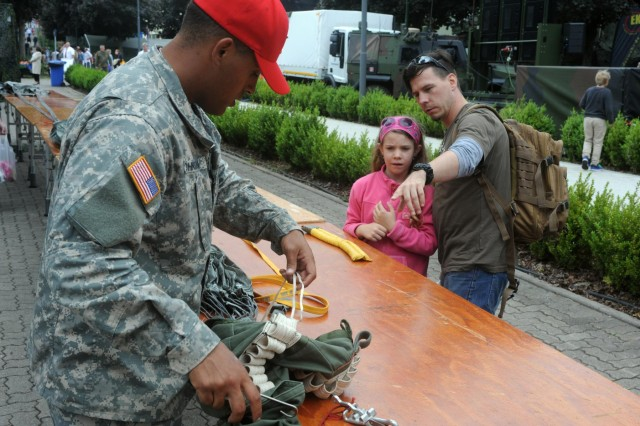 Mirko Meng, right, a German paratrooper and a native of Zweibrücken, Germany, explains to his daughter Nikka the way a parachute works while Pfc. Eric Johnson, a parachute rigger assigned to the 21st Theater Sustainment Command's 5th Quartermaster Company and a native of Fort Campbell, Ky., displays the Army T-10 parachute during the Rheinland-Pfalz Tag fair, June 22. (Photo by Staff Sgt. Alexander Burnett, 21st TSC Public Affairs)