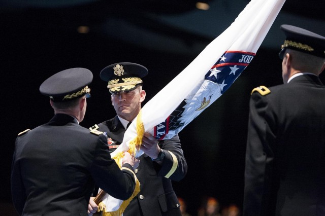 Incoming Commander of Joint Force Headquarters-National Capital Region and U.S. Army Military District of Washington Maj. Gen. Jeffrey S. Buchanan (center) receives a flag from Commander, North American Aerospace Defense Command and U.S. Northern Command Gen. Charles H. Jacoby, Jr. (left) during a change of command ceremony in Joint Base Myer-Henderson Hall's Conmy Hall June 24, 2013.