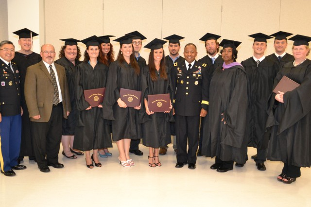 (From Left) Chaplain (Major) Young Kim, CECOM chaplain; Deputy to the Commanding General, Gary Martin; and Maj. Gen. Robert S. Ferrell, CECOM commander, stand amongst graduates of the Central Michigan University Human Resources Administration graduate certificate program June 18 at Aberdeen Proving Ground, Md