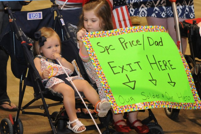 Briana Price, 3, right, waits for her father, Spc. David Price, prior to a welcome home ceremony for the 14th Combat Support Hospital June 19 at Freedom Hall. The members of the 14th CSH were reunited with their Families after a nine-month deployment to Afghanistan.