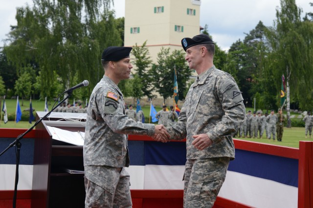 U.S. Army Brig. Gen. Walter E. Piatt, incoming commander of the 7th U.S. Army Joint Multinational Training Command,shakes hands with Col. Bryan L. Rudacille, outgoing JMTC commander, during a traditional change of command ceremony, June 26, at Grafenwoehr, Germany. In his new position, Piatt will spearhead training for U.S. and multinational forces. Annually, the JMTC trains approximately 12,000 soldiers, U.S., NATO, and partnered forces from Europe, Asia and Africa.