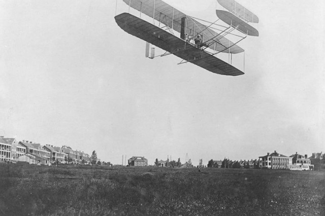 Orville Wright gives an exhibition flight in 1908 at an airfield in what was then called Fort Myer, Va. In the background are buildings that today are considered historic, including Wainwright Hall.