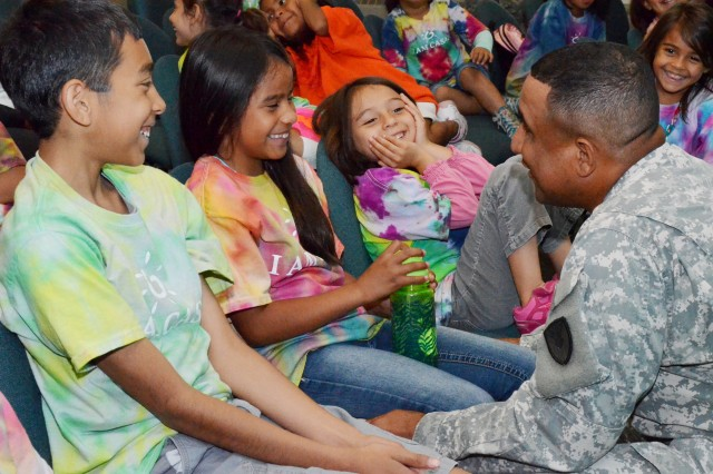 Capt. Ariel Rivera, Unit Equipping and Reuse Working Group team lead, Army Sustainment Command, sings a Spanish song to the children of Fiesta Camp at Rock Island Arsenal, Ill., June 19. (Photo by Elizabeth Adolphi, ASC Public Affairs)