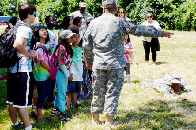 Staff Sgt. Richard Alexander, Material Management noncommissioned officer, Army Sustainment Command, and Spc. Brandon Wilson, Army Sustainment Command, teach the Fiesta Camp children how to evade the enemy by staying low to the ground. (Photo by Elizabeth Adolphi, ASC Public Affairs)