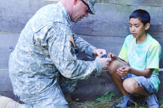 1st Sgt. William Rowley, Headquarters and Headquarters Company, Army Sustainment Command, teaches a child from Fiesta Camp how to handle a dummy grenade as part of the weapons display. (Photo by Elizabeth Adolphi, ASC Public Affairs)