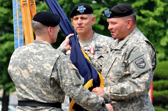Gen. James D. Thurman (right) passes the Eighth Army flag to Lt. Gen. Bernard S. Champoux during a change-of-command ceremony on Yongsan Garrison, South Korea, June 27, 2013.