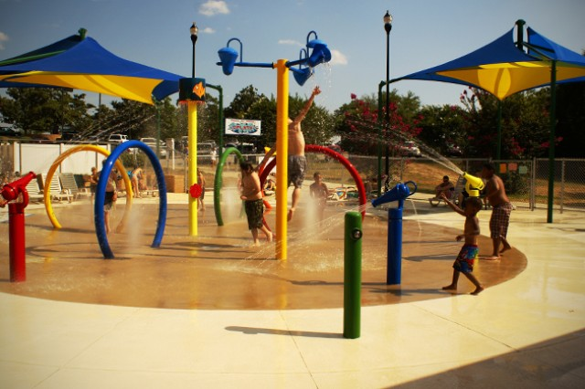 Children play in the spray area of Splash! Pool and Spray Park last year. The facility is now open to the general public.