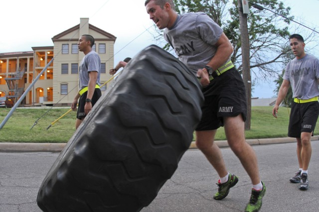 2nd Lt. Eric Shockley, 1st Battalion, 30th Field Artillery, a Soldier in the Pre-Ranger Course and student in the FA Basic Officer Leader Course, flips a 275-pound tire up hill as a part of a team-building workout during Ranger PT June 18, 2013, near Snow Hall.