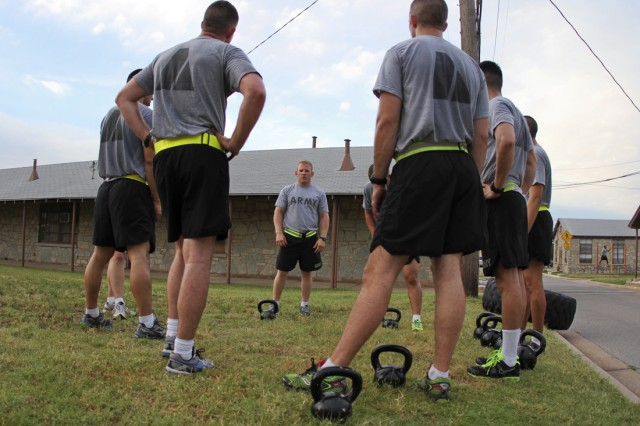 Capt. Timothy Palmer, a volunteer Pre-Ranger Course instructor, instructs Soldiers on how to do kettlebell swings for their last exercise during Ranger PT June 18, 2013, at Fort Sill.