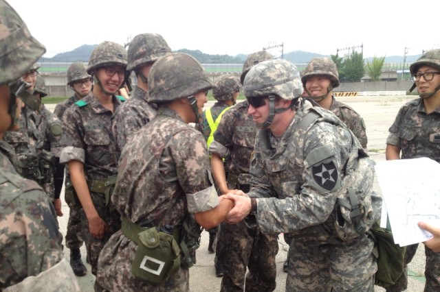 """GYEONGGI-DO, South Korea """" U.S. Soldiers from 70th Brigade Support Battalion, 210th Fires Brigade, 2nd Infantry Division, and Republic of Korea soldiers from the Supply and Transportation Battalion, 28th Division, pose for a photo before conducting a joint convoy operation from Camp Mobile to the Mae San Ri Drop Zone June 19, 2013. The airdrop mission was cancelled because of inclement weather, but the two armies had a chance to get to know each other, build positive relationships, and strengthen the U.S.-ROK alliance to defend Republic of Korea from any threat. (Photo courtesy of 2nd Lt. Max Tresnak)."""