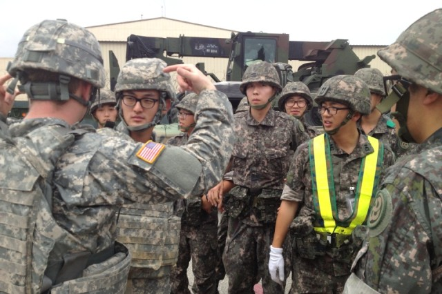 """GYEONGGI-DO, South Korea """" U.S. Soldiers from 70th Brigade Support Battalion, 210th Fires Brigade, 2nd Infantry Division, and Republic of Korea soldiers from the Supply and Transportation Battalion, 28th Division, get to know each other June 19, 2013. The units were scheduled to conducted a joint convoy operation from Camp Mobile to the Mae San Ri Drop Zone and perform air drop recovery operations together. The airdrop mission was cancelled because of inclement weather, but the two armies had a chance to get to know each other, build positive relationships, and strengthen the U.S.-ROK alliance to defend Republic of Korea from any threat. (Photo courtesy of 2nd Lt. Max Tresnak)."""