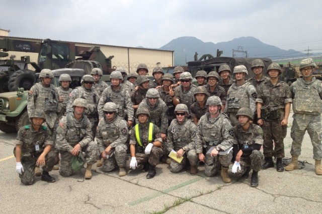 """GYEONGGI-DO, South Korea """" U.S. Soldiers from 70th Brigade Support Battalion, 210th Fires Brigade, 2nd Infantry Division, and Republic of Korea soldiers from the Supply and Transportation Battalion, 28th Division, pose for a group photo June 19, 2013. The units were scheduled to conduct a joint convoy operation from Camp Mobile to the Mae San Ri Drop Zone and perform air drop recovery operations together. The airdrop mission was cancelled because of inclement weather, but the two armies had a chance to get to know each other, build positive relationships, and strengthen the U.S.-ROK alliance to defend Republic of Korea from any threat. (Photo courtesy of 2nd Lt. Max Tresnak)."""