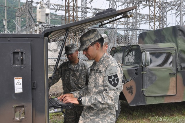 """CAMP CASEY, South Korea """" Sgt. John Rodriguez from Hawaii, a multichannel transmission systems operator-maintainer, assigned to Headquarters and Headquarter Battery, 210th Fires Brigade connects and tests communications equipment on Camp Casey, South Korea June 27, 2013. Soldiers upgrade a modem, set up and test the equipment, and determine whether they are ready to go. This training shows signal Soldiers' readiness to support our force to """"Fight Tonight."""" (U.S. Army photo by Cpl. Kim Han-byeol, 210th Fires Brigade public affairs specialist/Released)."""