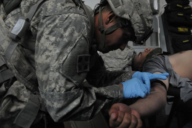 Sgt. Michael Mordes, healthcare specialist, Headquarters and Headquarters Company, 1st Battalion, 22nd Infantry Regiment, 1st Armored Brigade Combat Team, 4th Infantry Division, inserts an IV into the arm of a simulated patient, during Raider Response, June 13, 2013. (U.S. Army photo by Spc. Andrew Ingram, 1st ABCT PAO, 4th Inf. Div.)