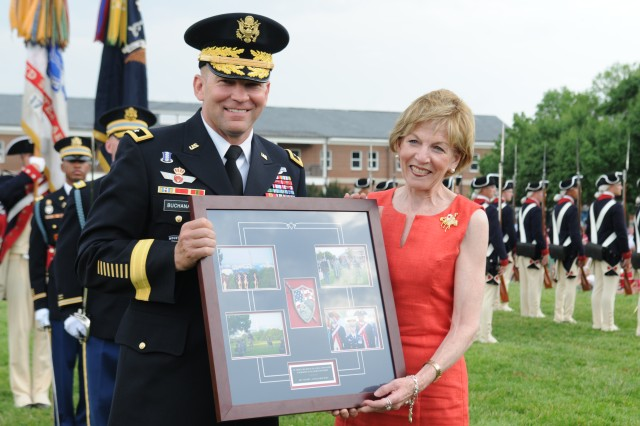 Maj. Gen. Jeffrey S. Buchanan presents the Chief Executive Officer for the Red Cross in the National Capital Region, Ms. Linda Mathes, a memento in appreciation for her organizations humanitarian efforts.  The American Red Cross in the National Capital Region received the special recognition during the U.S. Army Military District of Washington's production of Twilight Tattoo at Joint Base Myer - Henderson Hall, June 26, 2013.