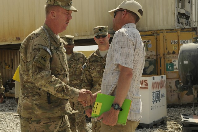 Maj. Gen. Kenneth Dowd (left), the director of logistical operations for the Defense Logistics Agency greets Mr. David Flietstra (right), the area manager for the Defense Logistics Agency Disposition Services (DLA-DS) Afghanistan at Bagram Airfield, Afghanistan, June 27, 2013. Multiple joint senior logisticians walked through the Defense Logistics Agency disposition services yard to review operations and identify ways to accelerate support of disposition and drawdown of equipment.