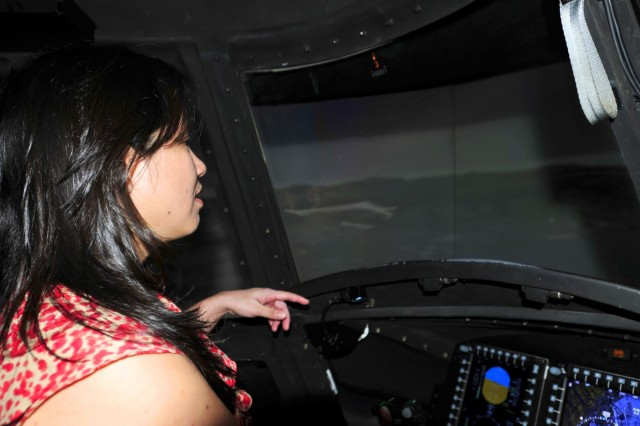 Kristen Yamane, a corporate development planner with the Queen's Health Systems, scans the area ahead of her as she flies in the CH-47 Chinook simulator during a visit to the 25th Combat Aviation Brigade, 25th Infantry Division, to learn about the Army's risk management process for its pilots on Wheeler Army Airfield, Hawaii, June 12.