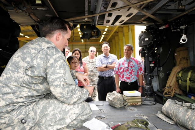 Staff Sgt. Lee Hockersmith, a flight medic assigned to Company C, 3rd Battalion, 25th Aviation Regiment, 25th Combat Aviation Brigade, briefs medical officials from Queens Medical Center about the medical procedures in a UH-60 MEDEVAC Black Hawk during a visit to the 25th CAB, 25th Infantry Division on Wheeler Army Airfield, Hawaii, June 12.
